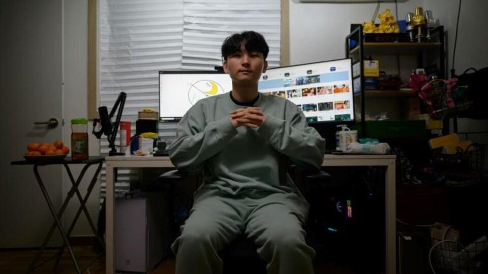 Un homme prend la pose devant ses écrans d'ordinateur.