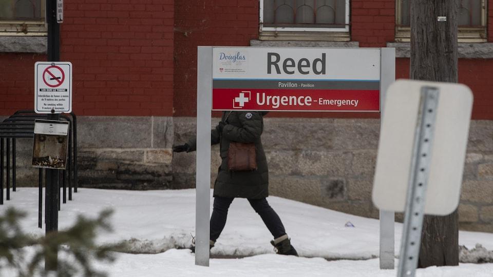 Une femme marche derrière un panneau annonçant l'urgence.