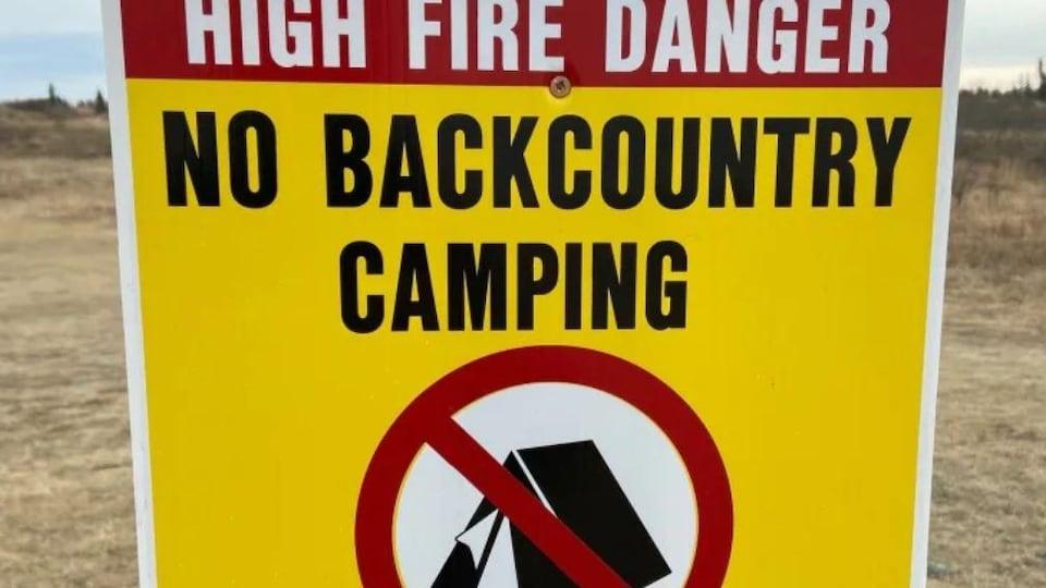 Une affiche au fond jaune sur laquelle il est inscrit «NO BACKCOUNTRY CAMPING» avec un logo d'interdiction sur une tente.