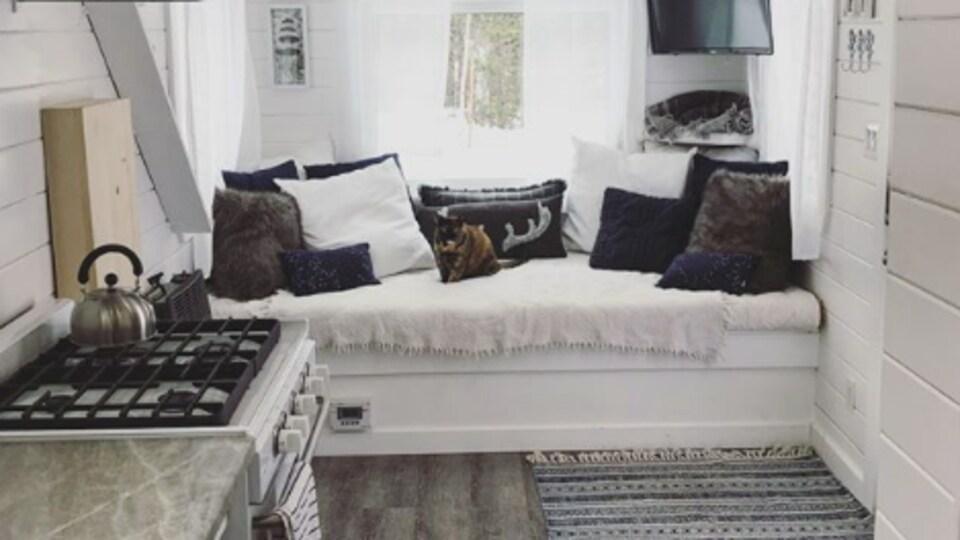 L'intérieur d'une mini-maison avec espace cuisine, un lit et un coin salon.