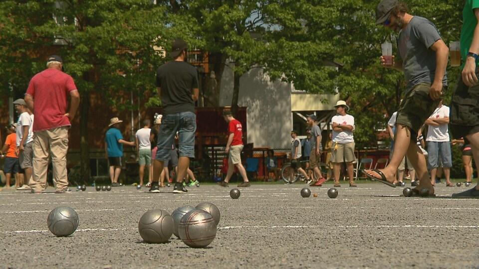Gros plan sur des boules de pétanque proches les unes des autres sur un terrain extérieur avec des gens en arrière-plan.