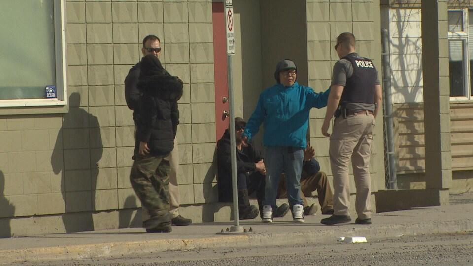 La police en interaction avec une femme alors que d'autres personnes sont autour.
