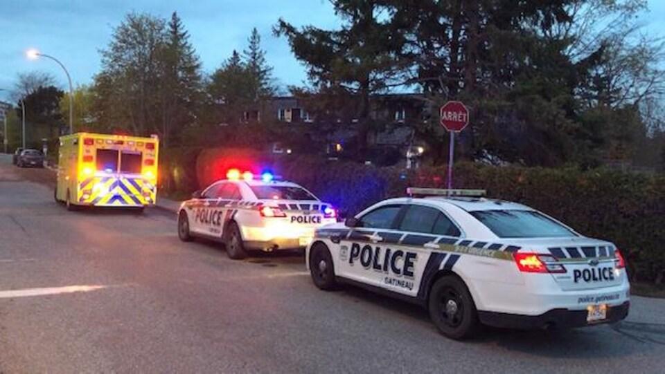 Deux auto-patrouilles stationnées derrière une ambulance.