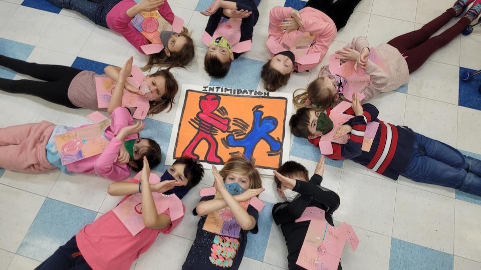 Des écoliers couchés au sol qui font un X avec leurs bras pour dire non à l'intimidation