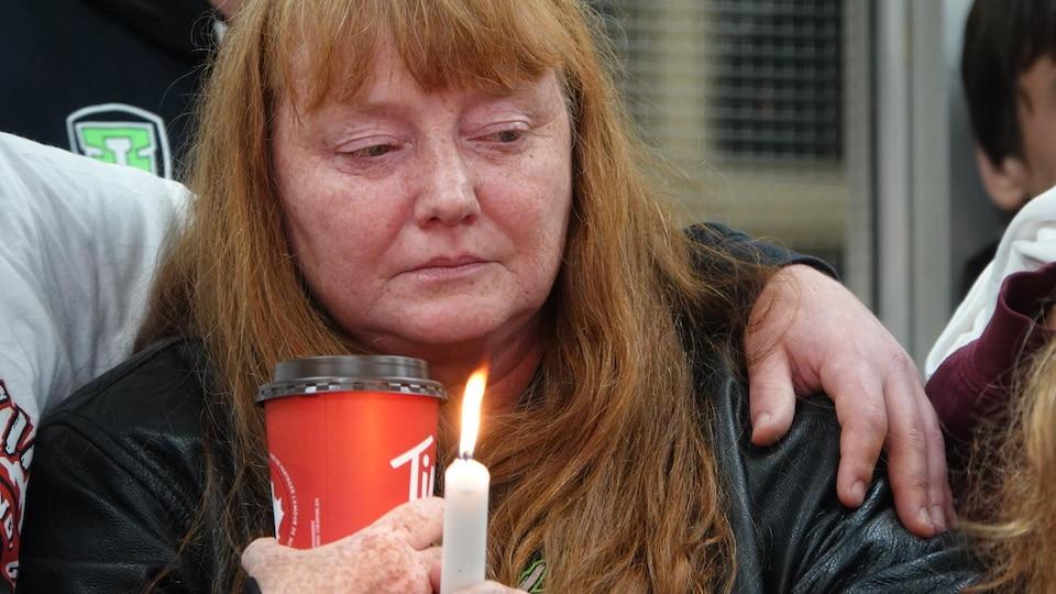 Une femme est triste et tient une bougie à la mémoire de son fils.