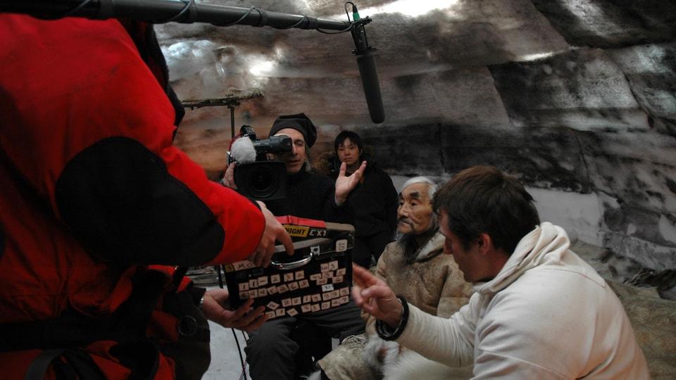 Dans un igloo, un aîné inuit est entouré d'un caméra man, d'un perchiste et d'un autre homme qui tient le clap.