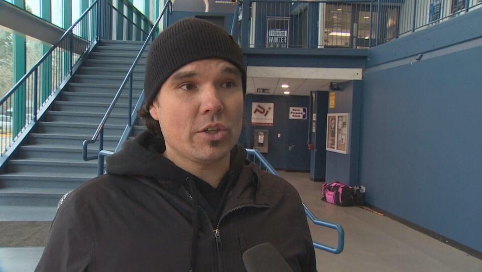 Un homme s'adresse à un journaliste dans un aréna de Burnaby, dans le Grand Vancouver.
