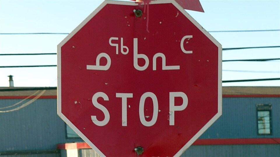 Un panneau d'arrêt à Iqaluit avec les indications écrites en anglais et en inuktitut