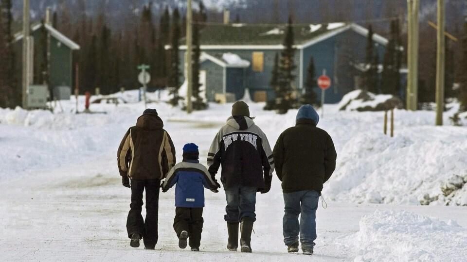 Quatre personnes marchent le long d'une rue.
