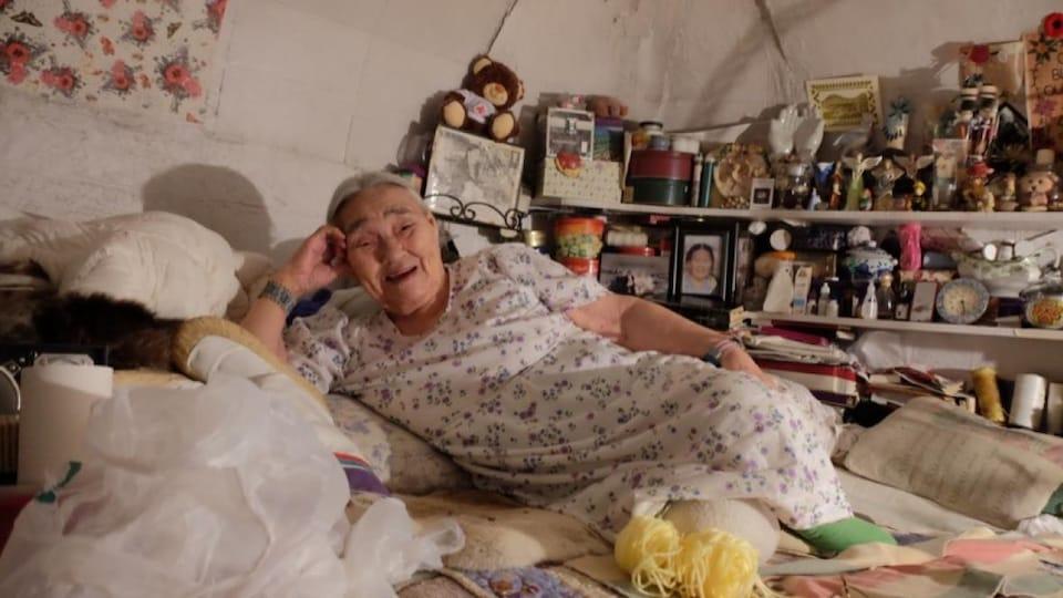 Un portrait de Qaapik Attagutsiak, allongée sur son lit, dans sa maison d'Arctic Bay.