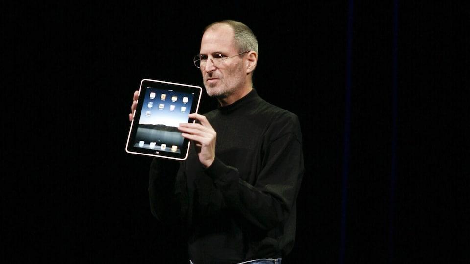 Steve Jobs tient un iPad dans ses mains sur scène.