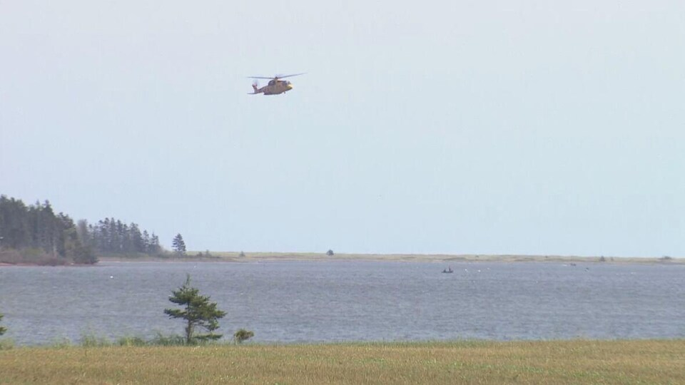 Un hélicoptère Cormorant survole une étendue d'eau où naviguent également des bateaux.