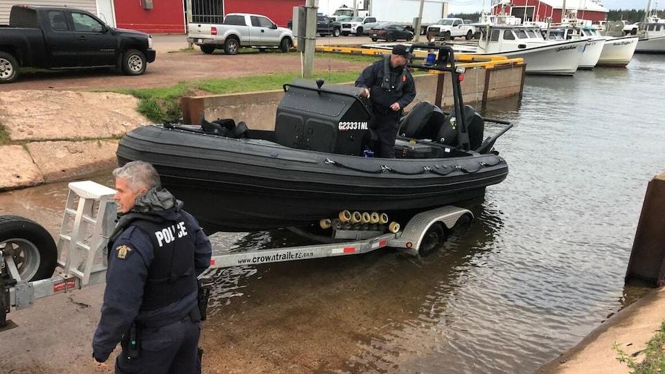 Deux agents de la GRC mettent un bateau de recherche à l'eau.