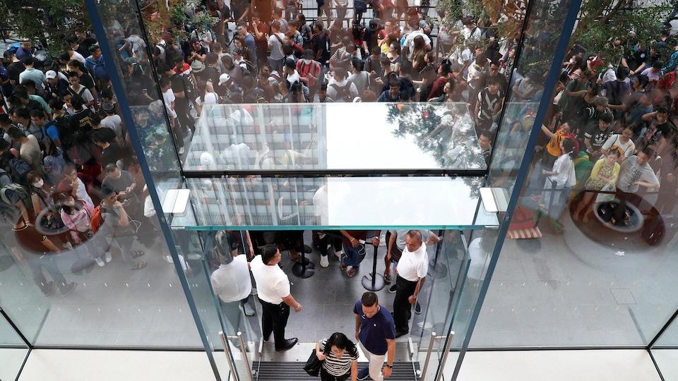 Une femme vue en plongée, entre dans un magasin Apple, alors qu'une file de personnes attendant à l'extérieur du magasin pour pouvoir rentrer.