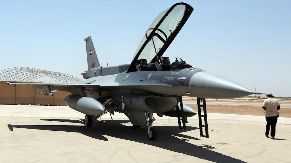 Un avion de chasse stationné sur une base aérienne.