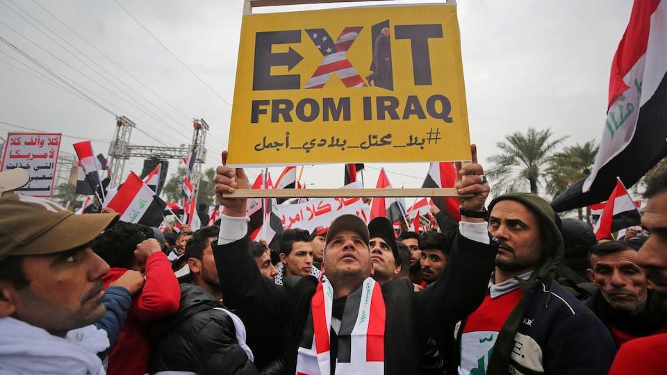 « Sortez d'Irak », peut-on lire sur une pancarte brandie par un manifestant. Des images du drapeau américain et du président Donald Trump sont visibles sur la pancarte.