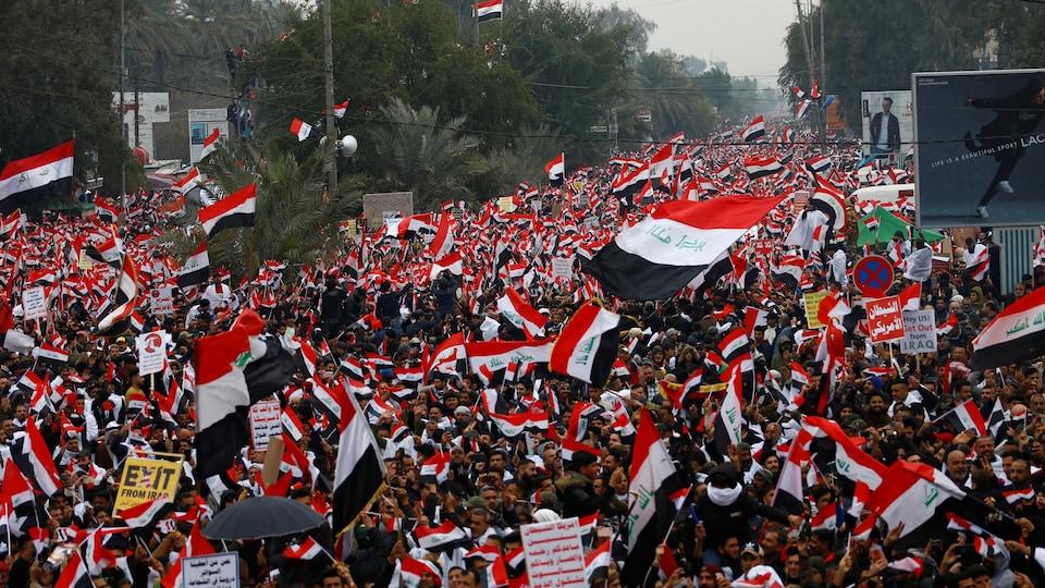 Une mer de monde est visible dans une rue de Bagdad. Les drapeaux irakiens sont à l'honneur.