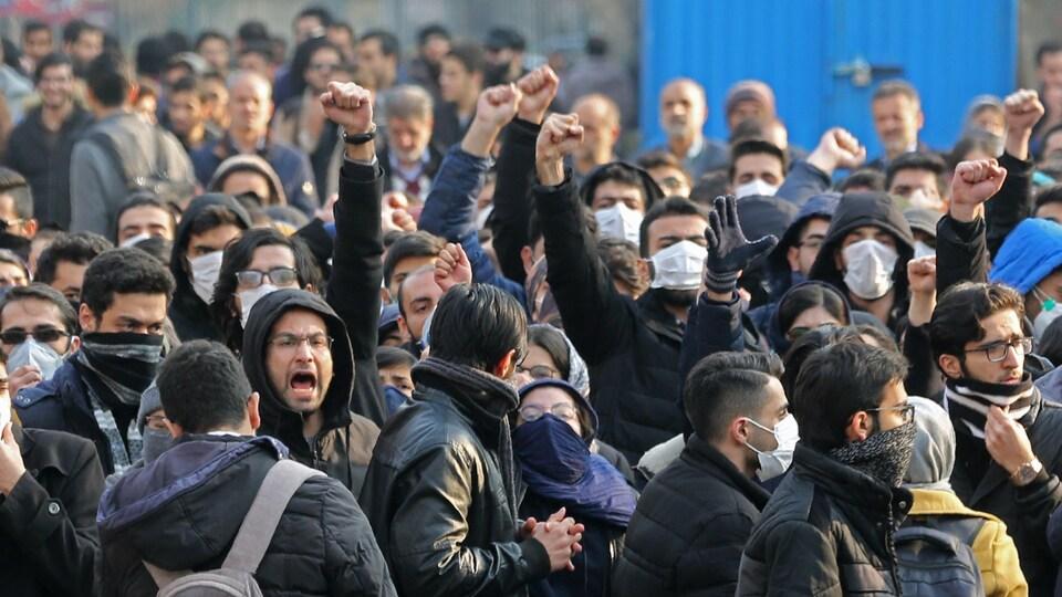 Des dizaines d'étudiants, masqués pour la plupart, crient des slogans ou brandissent un poing en l'air.