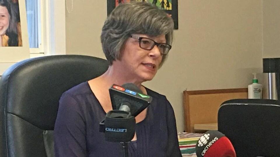 Une femme parle aux journalistes.