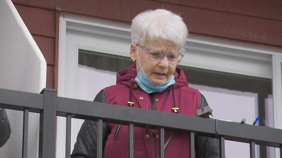 Irène Fortin discute depuis son balcon.