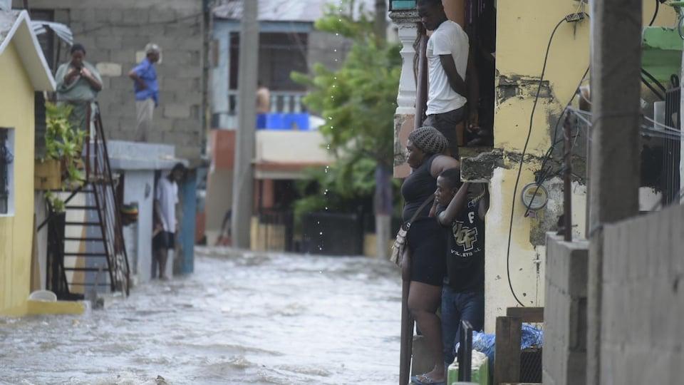 Des gens regardent la rue inondée.