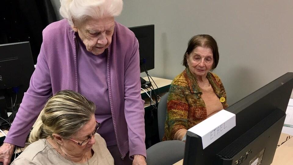 Une ainée aide deux femmes assises à des ordinateurs.