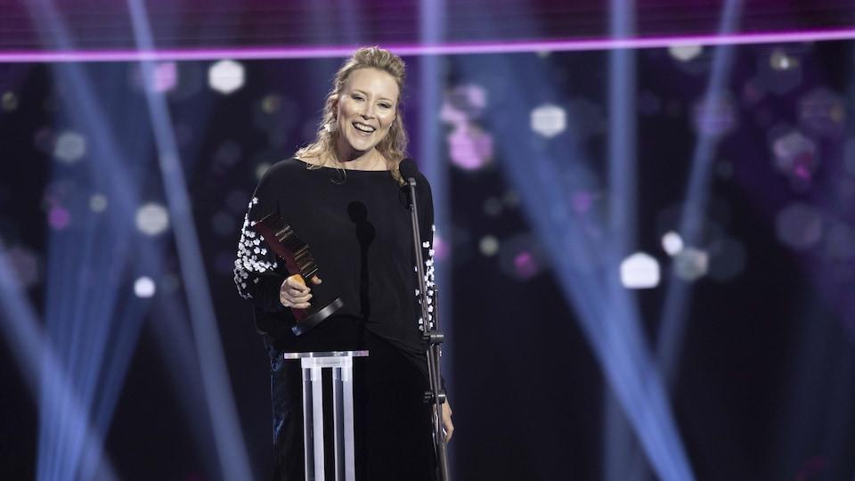 Une femme souriante tient un trophée Gémeaux devant un piédestal sur scène.