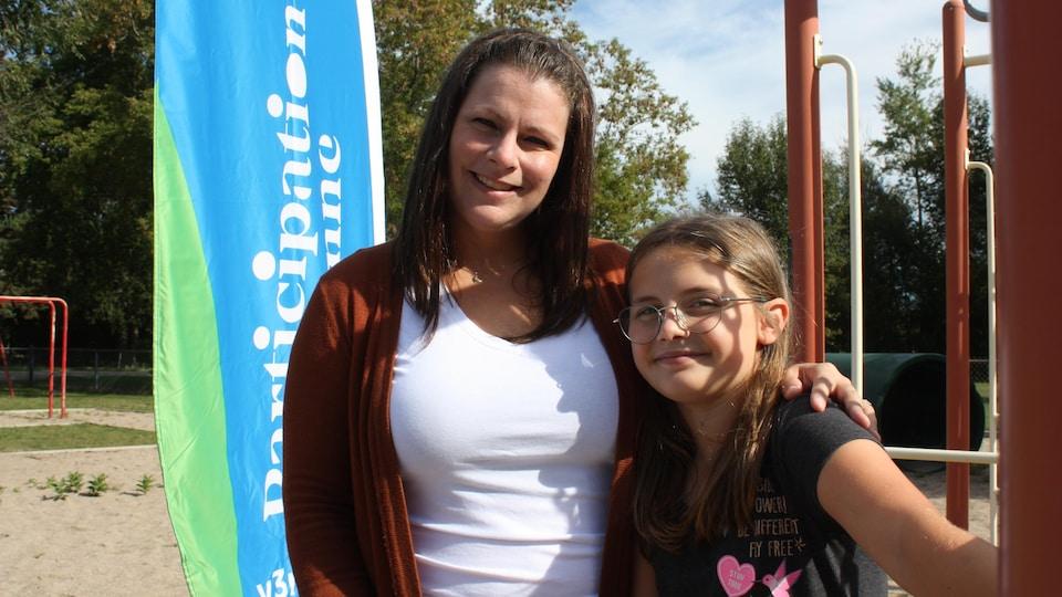 Isabelle Dauphinais et une fillette prennent la pose devant une banderole avec l'inscription « Participation citoyenne ».