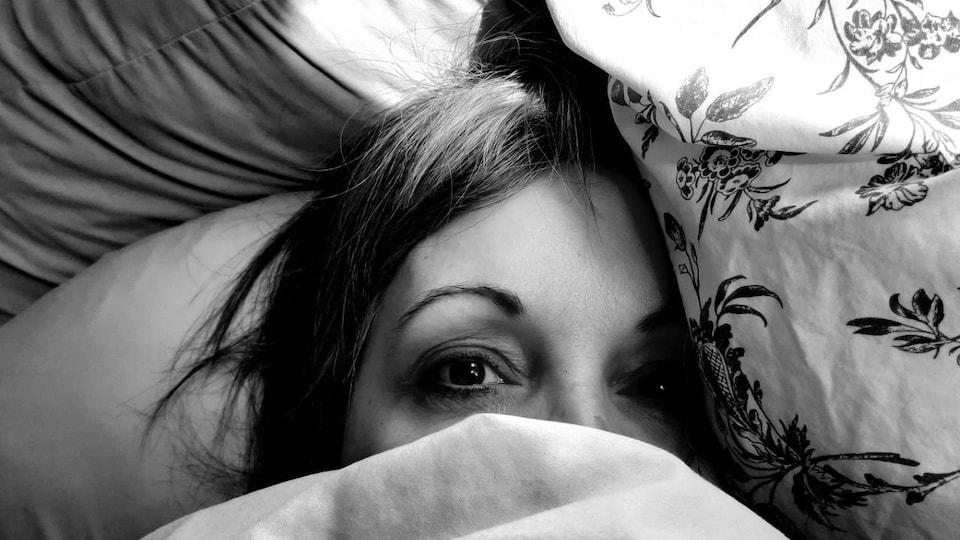 Le haut du visage d'Isabelle Dumais, qui est dans son lit, sous les draps.