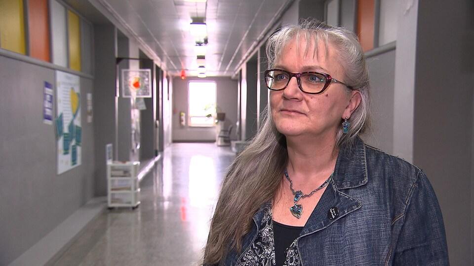 Isabelle Fortin est debout dans un couloir. Elle regarde la caméra.