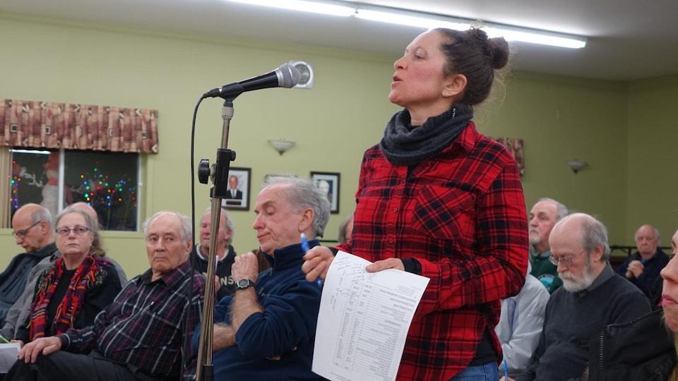 Isabelle Héroux debout, au micro, devant d'autres citoyens