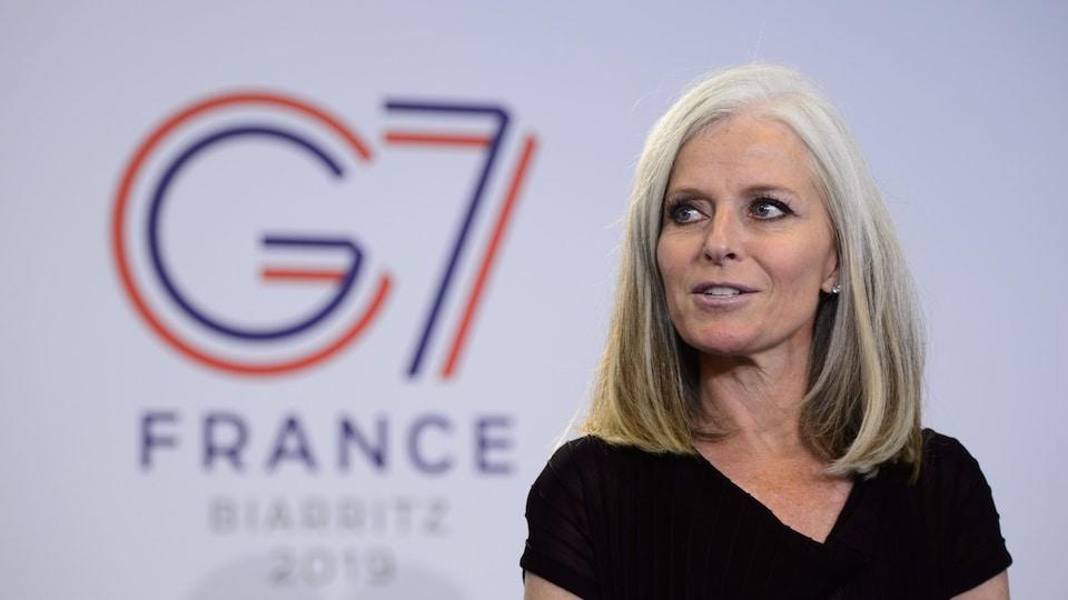 Isabelle Hudon prend la parole devant un mur arborant le logo G7 France Biarritz 2019.