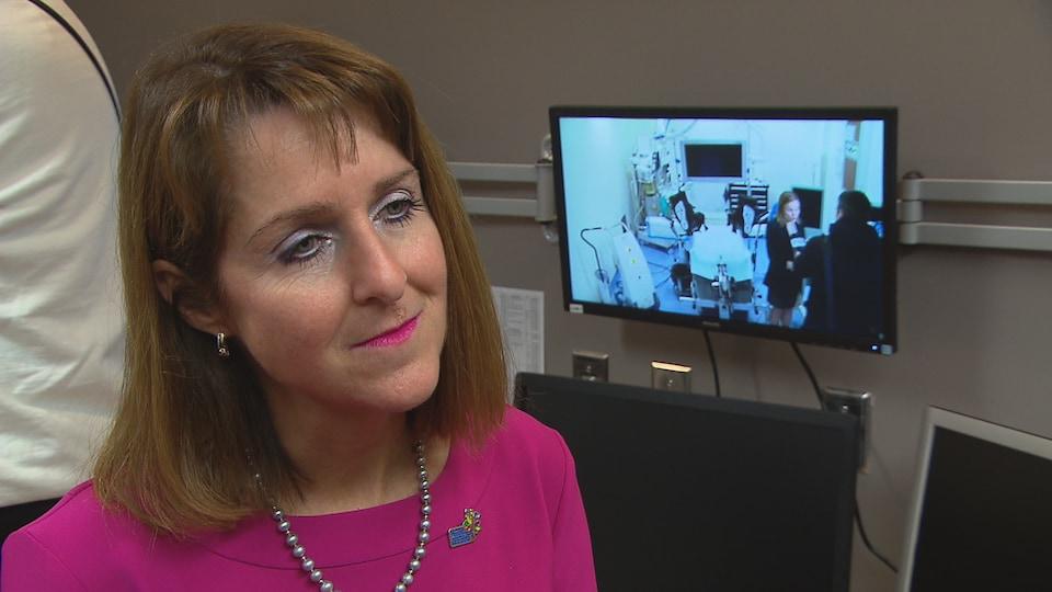 Isabelle Malo devant des écrans d'ordinateur.