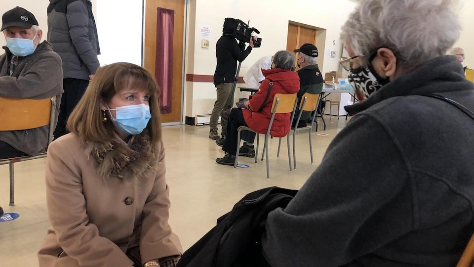 Isabelle Malo est accroupie devant une dame assise sur une chaise. Elles discutent alors que la dame attend de se faire vacciner