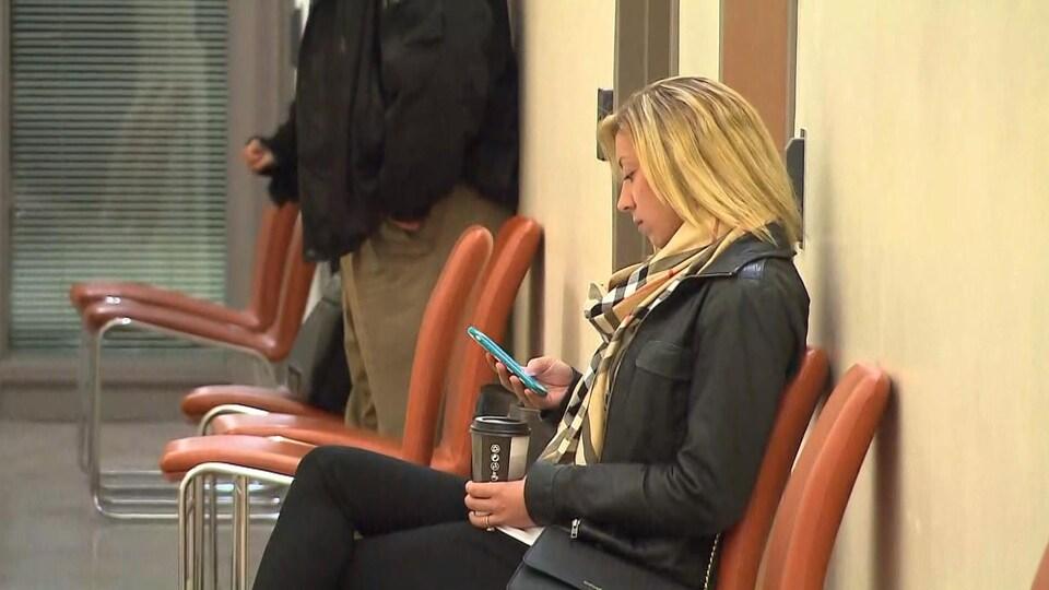 Alexandra Mongeau, assise, consulte son téléphone cellulaire.