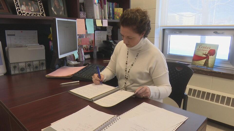 Isabelle Savoie-Jamieson est à son bureau. Elle écrit sur un cahier avec un stylo bleu.