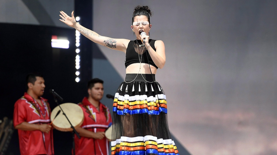 Une jeune femme habillée d'une jupe noire et multicolore chante les yeux fermés et un bras ouvert.