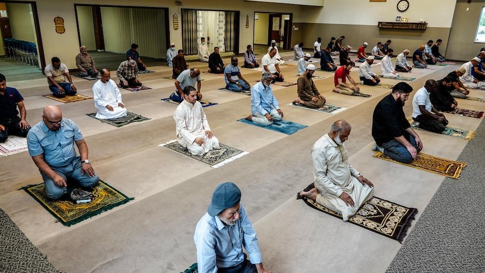 Des personnes religieuses sont agenouillées sur leur tapis de prière dans un sanctuaire en gardant de l'espace entre eux.