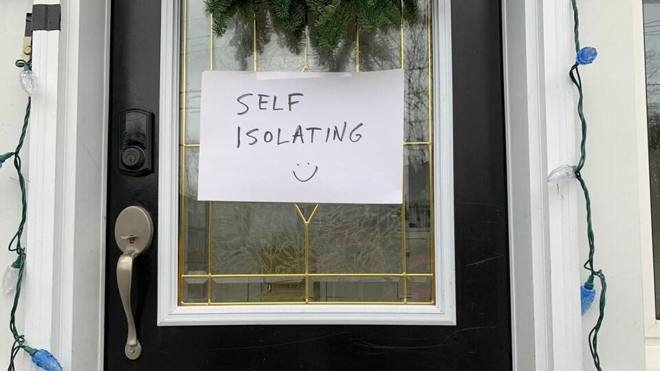 Une porte fermée sur laquelle on peut lire : self isolating.