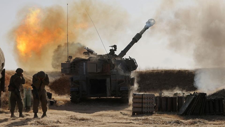 Des soldats se bouchent les oreilles et se mettent en retrait tandis qu'un lance-roquette fait feu.