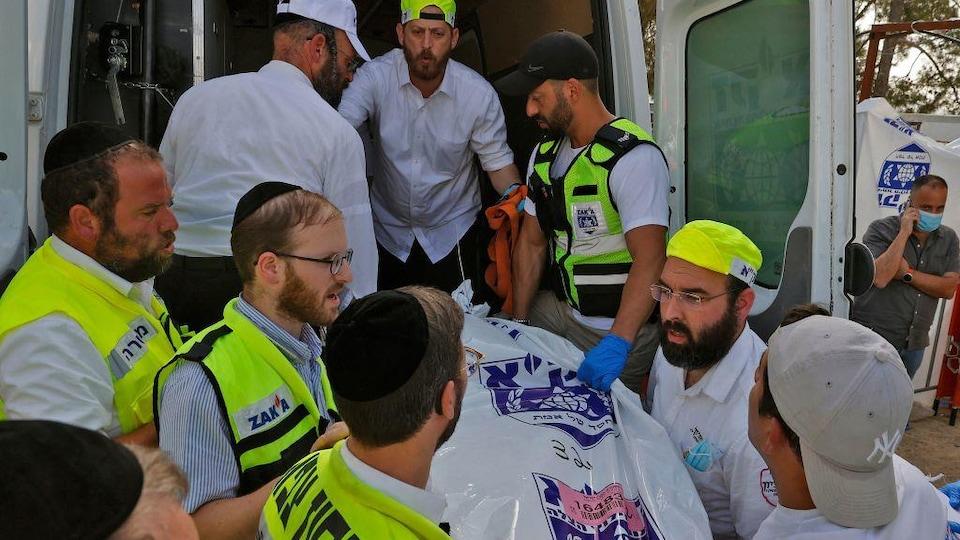Des secouristes s'entassent à la porte arrière d'une ambulance. Un corps dans un sac en plastique est transporté à l'intérieur du véhicule.