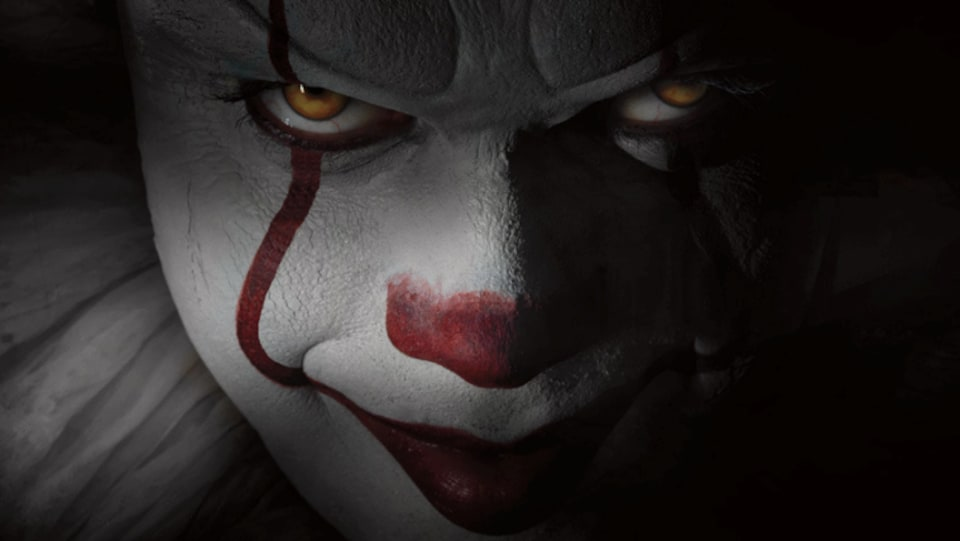 Un gros plan sur le visage de Bill Skarsgård maquillé en clown effrayant.