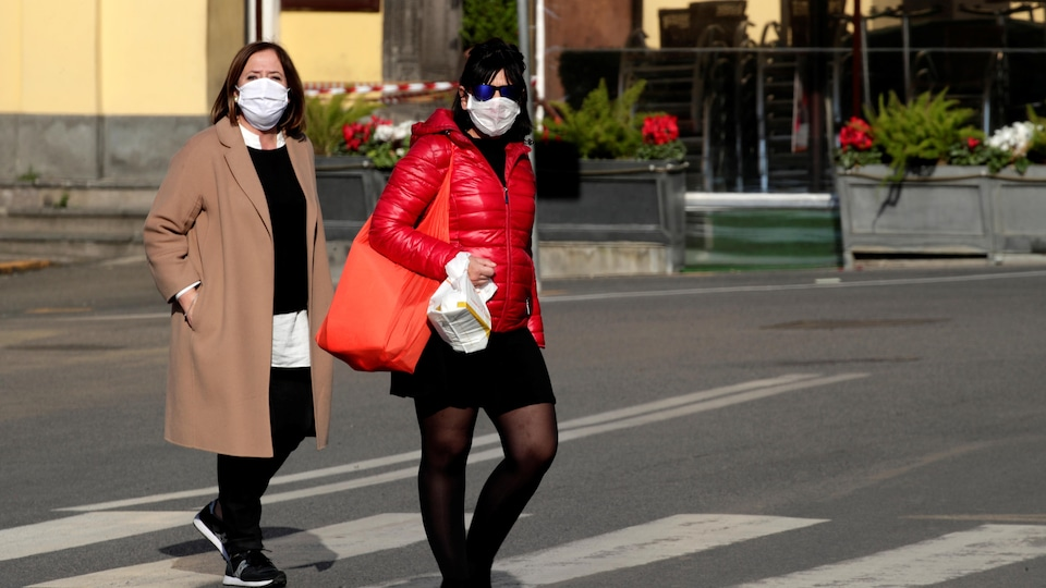Deux femmes portant des masques traversent la rue.