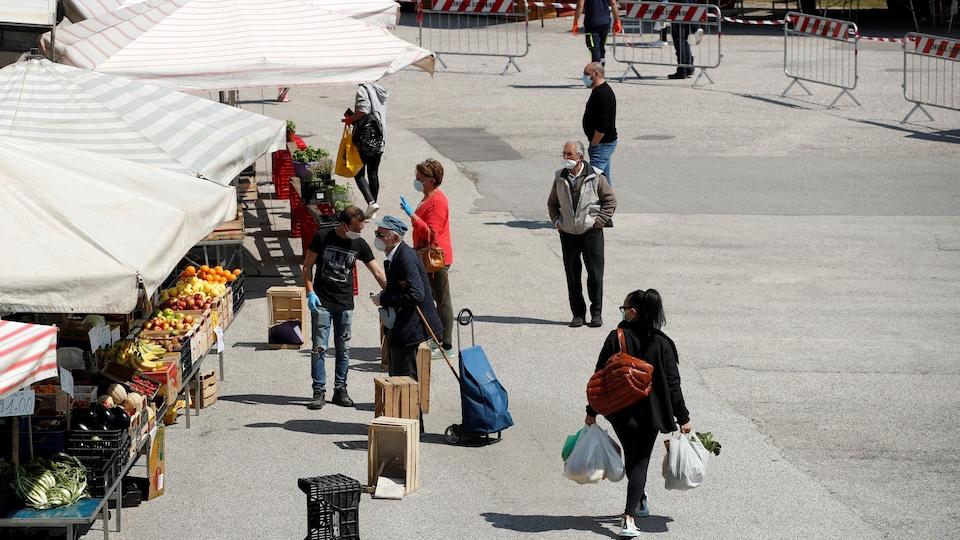 Des personnes portant des masques de protection dans un marché.