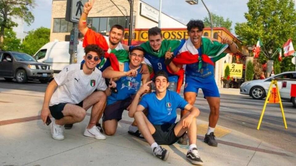Six hommes habillés aux couleurs de l'Italie faisant le signe de numéro un avec leurs doigts. Ils festoient sur un trottoir.