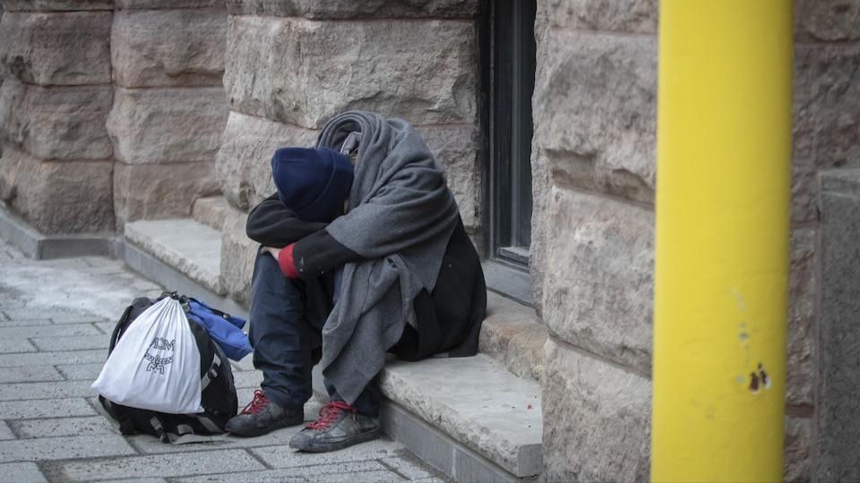 Image d'un itinérant dans les rues de Montréal.  Photo prise dans le centre-ville de Montréal, Québec, Canada.