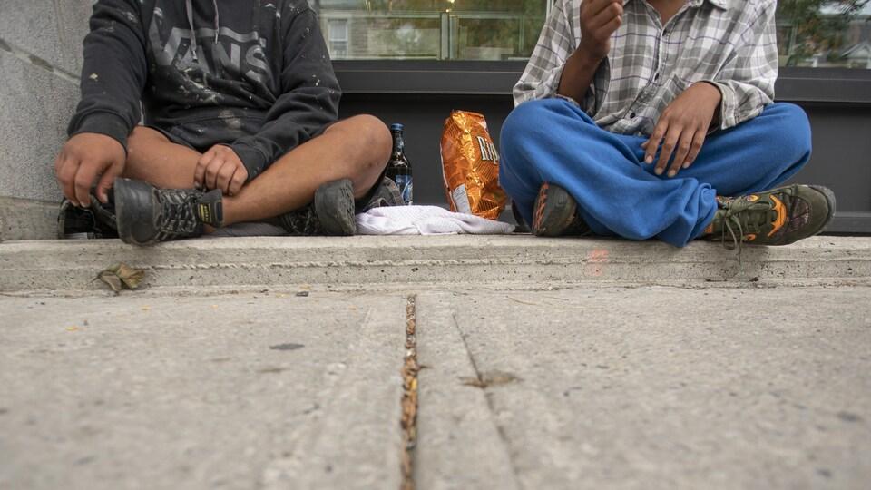 Deux personnes dont on ne voit que les jambes sont assises sur un trottoir.