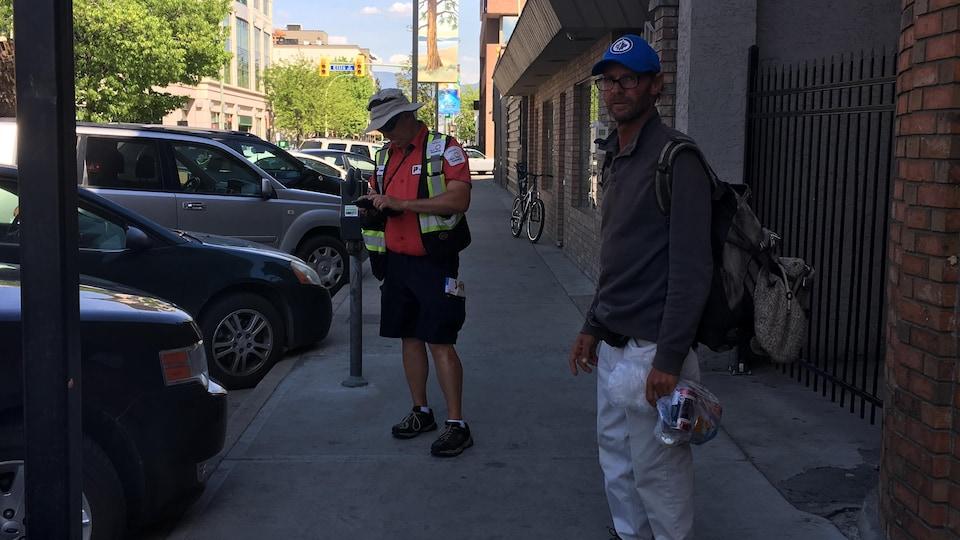 À l'avant-plan un homme qui porte une casquette, des bottes de randonnée et tient un sac avec des canettes vides. Près de lui un employé de la Ville de Kelowna vérifie un parcomètre.