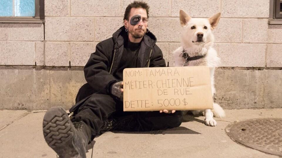 Un sans-abri avec son chien et une affiche qui dit qu'il a une dette de 5000 $