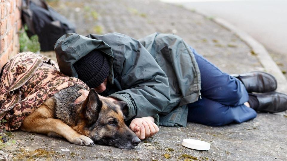 Un sans-abri et son chien dorment sur le trottoir.